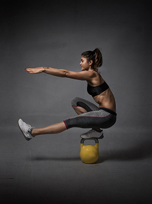 woman balancing in a kettlebell