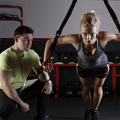 woman exercising on pull up straps with man in green shirt kneeling on her left