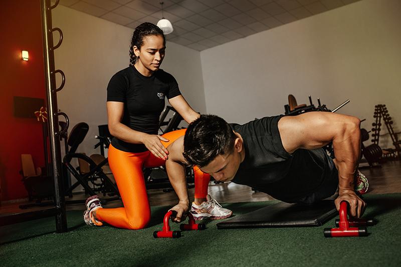 woman helping man do pushups
