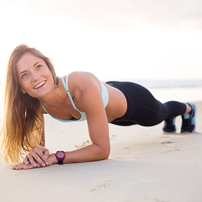 woman exercising on beach with smartwatch